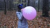 Blowing-pink-Gemar-balloon-18-with-flower-print-in-a-late-Autumn-park-no-pop